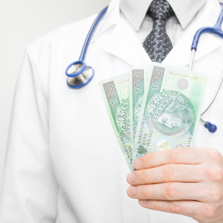doctor holding money: Doctor holding money in his hand - 1 to 1 ratio