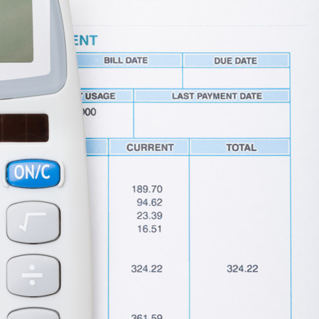 utility payments: Calculator next to bill - studio shot