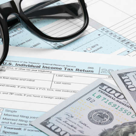 taxable: US Tax Form 1040 with dollars and glasses Stock Photo
