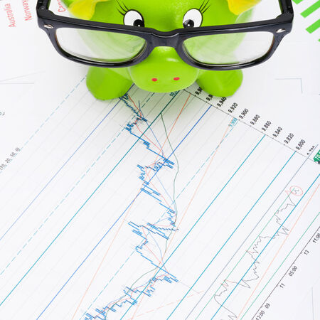 Green piggy bank over stock chart - view from top photo