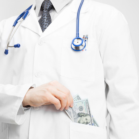 Doctor putting money into his pocket photo