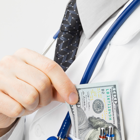 doctor putting money: Medical doctor putting money into his pocket - studio shoot