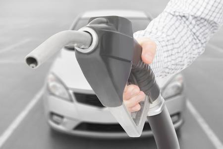 petrochemistry: Negro color del arma bomba de combustible en la mano con el coche en el fondo