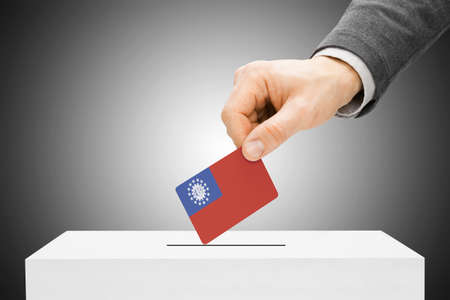 polling booth: Voting concept - Male inserting flag into ballot box - Burma Stock Photo