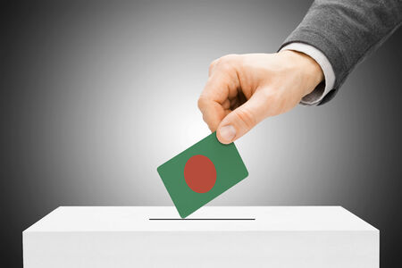 electoral system: Voting concept - Male inserting flag into ballot box - Bangladesh Stock Photo