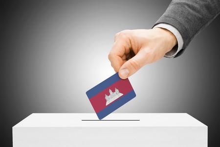 Voting concept - Male inserting flag into ballot box - Cambodia Stock Photo