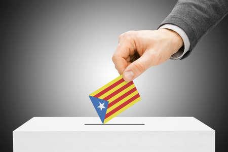 poll: Voting concept - Male inserting flag into ballot box - Catalonia Stock Photo