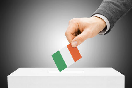 Voting concept - Male inserting flag into ballot box - Ireland Stock Photo