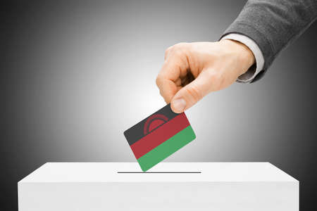 malawian flag: Voting concept - Male inserting flag into ballot box - Malawi