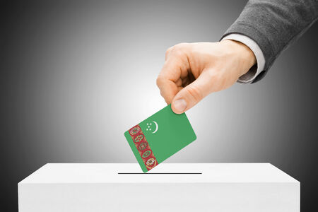 electoral system: Voting concept - Male inserting flag into ballot box - Turkmenistan