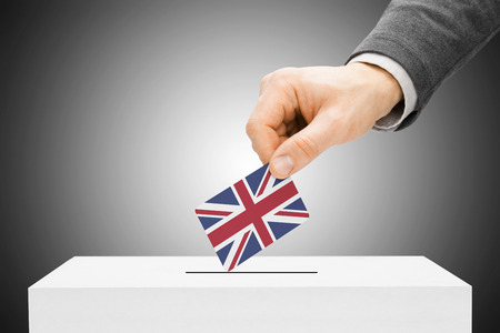 local election: Voting concept - Male inserting flag into ballot box - United Kingdom
