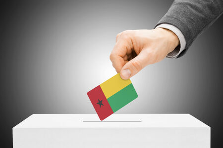 electoral system: Voting concept - Male inserting flag into ballot box - Guinea-Bissau Stock Photo