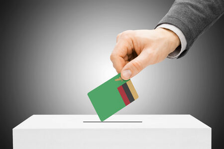 zambian: Voting concept - Male inserting flag into ballot box - Zambia