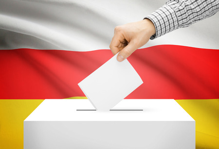 electoral: Voting concept - Ballot box with national flag on background - South Ossetia