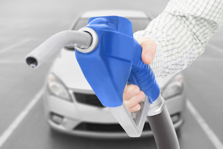 methanol: Blue color fuel pump gun in hand with car on background