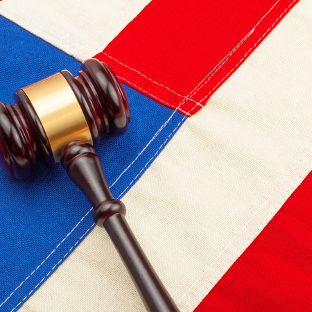 Wooden judge gavel over US flag - court judgment concept photo