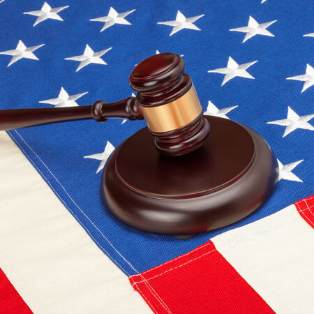 Wooden judge gavel and soundboard laying over US flag - court judgment concept photo