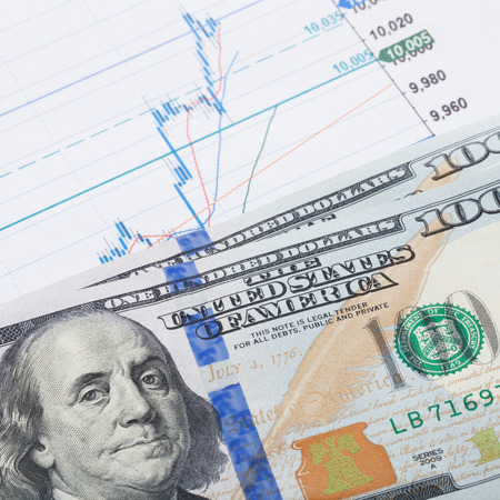 brent crude: Stock market chart and 100 USA dollars banknote over it - market concept