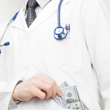 doctor putting money: Doctor putting money into his pocket - health care concept