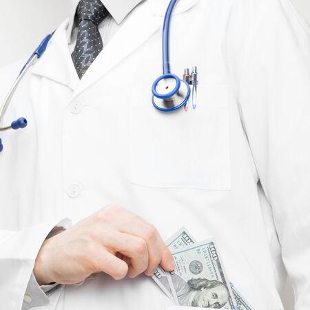 doctor putting money: Doctor putting money into his pocket - health care concept