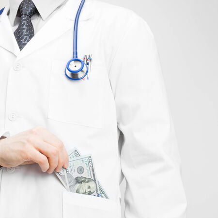 putting money in pocket: Doctor putting money into his pocket with his left hand - health care concept Stock Photo