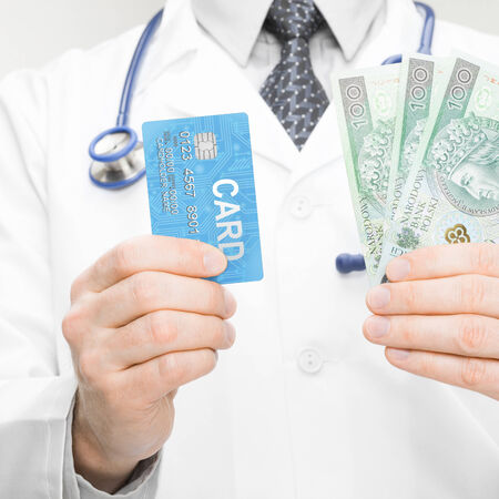 doctor holding money: Doctor holding money and credit card in his hand - health care concept