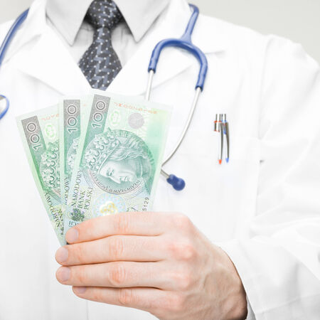 corruptible: Doctor holding money in his hand - health care concept Stock Photo