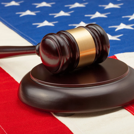 Wooden judge gavel and soundboard laying over USA flag - court judgment concept photo