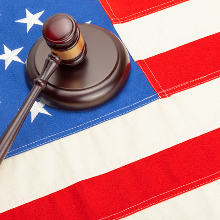international criminal court: Wooden judge gavel and soundboard laying over US flag - court judgment concept Stock Photo