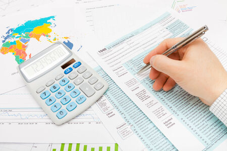 filling out: Man filling out 1040 US Tax Form Stock Photo