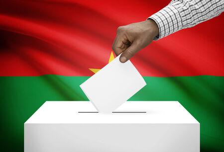 political system: Ballot box with national flag on background - Burkina Faso Stock Photo
