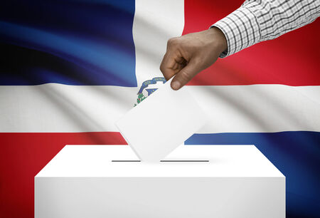 electoral system: Ballot box with national flag on background - Dominican Republic Stock Photo