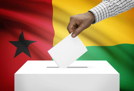 political system: Ballot box with national flag on background - Guinea-Bissau