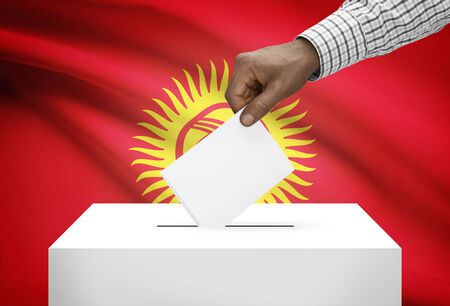 electoral system: Ballot box with national flag on background - Kyrgyzstan Stock Photo