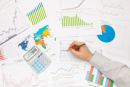 market trends: Business man working with financial data - pen in hand