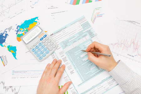 taxable income: Male filling out 1040 US Tax Form with silver pen Stock Photo