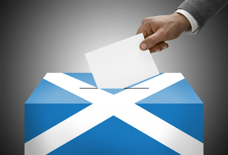 electoral system: Ballot box painted into national flag colors - Scotland Stock Photo