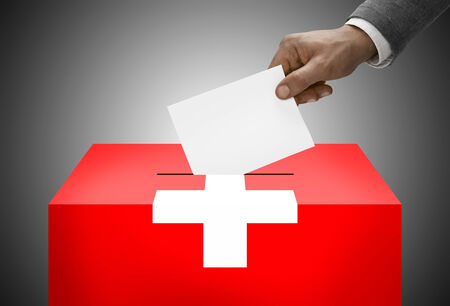 plebiscite: Ballot box painted into national flag colors - Switzerland Stock Photo
