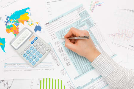 filling out: Male filling out 1040 US Tax Form with lots of financial documents around Stock Photo