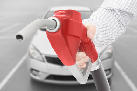 methanol: Red color fuel pump gun in hand with car on background