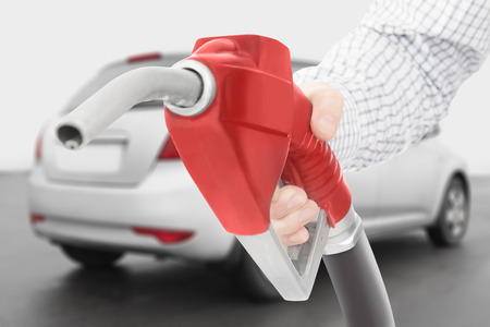 petrochemistry: Red color fuel pump gun in hand with grey car on background Stock Photo