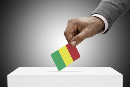 elect: Ballot box painted into national flag colors - Mali Stock Photo