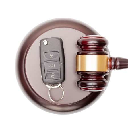 car crime: Wooden judge gavel and car keys over sound box - studio shot Stock Photo