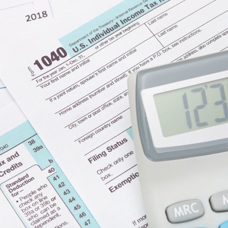 taxable income: Calculator over US 1040 Tax Form - studio shot Stock Photo