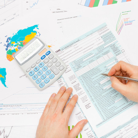 taxable: Male filling out 1040 US Tax Form with silver pen - studio shot Stock Photo