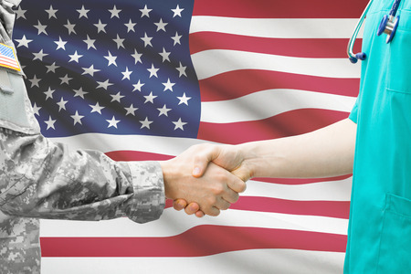 military uniform: Soldier and doctor shaking hands with flag on background - United States