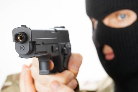 Man in black mask holding gun in front of him Stock Photo