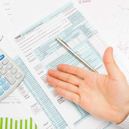 taxable income: US 1040 Tax Form, calculator and male hand