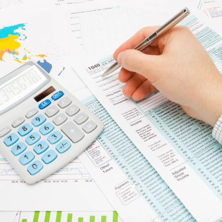 taxable income: Male filling out 1040 US Tax Form with lots of financial documents around Stock Photo