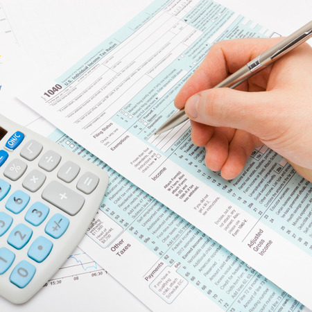 taxable: US 1040 Tax Form and pen in hand